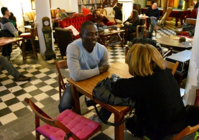 "Cameroonian Ibrahima Yonga speaks to a woman about escaping the Boko Haram group in Cameroon and spending months at sea in a bid to reach Europe, during an event titled ""Human Library"" organised by a Cypriot NGO at a cafe Nicosia, on February 7, 2016"