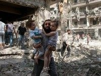 A Syrian man carries his two girls across rubble following a barrel bomb attack on Aleppo's rebel-held al-Kalasa neighbourhood