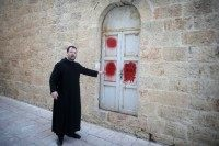 Father Nikodemus Schnabel, spokesperson of the Dormition Abbey, points towards anti-Christian graffiti in Hebrew, on the Church of the Dormition, one of Jerusalem's leading pilgrimage sites, outside of the Old City of Jerusalem, on January 17, 2016