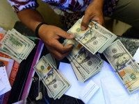 An Indonesian money changer sorts US dollar bills in Jakarta on March 13, 2015.