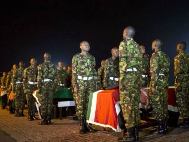FILE - In this Monday, Jan. 18, 2016 file photo, military pallbearers stand to attention next to the coffins of four Kenyan soldiers who were killed in an attack by al-Shabaab in Somalia, at a ceremony to receive their bodies which were airlifted to Wilson Airport in Nairobi, Kenya. The number of deadly attacks by Islamic extremists is mounting across Africa, raising questions about the resurgence of armed groups once seen to be in decline. (AP Photo/Ben Curtis, File)