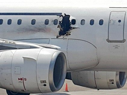 In this Tuesday, Feb. 2, 2016 photo, a hole is photographed in a plane operated by Daallo Airlines as it sits on the runway of the airport in Mogadishu, Somalia. A gaping hole in the commercial airliner forced it to make an emergency landing at Mogadishu's international airport late Tuesday, …