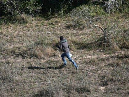 An undocumented immigrant runs from U.S. Border Patrol agents on December 9, 2015 near McAllen, Texas.