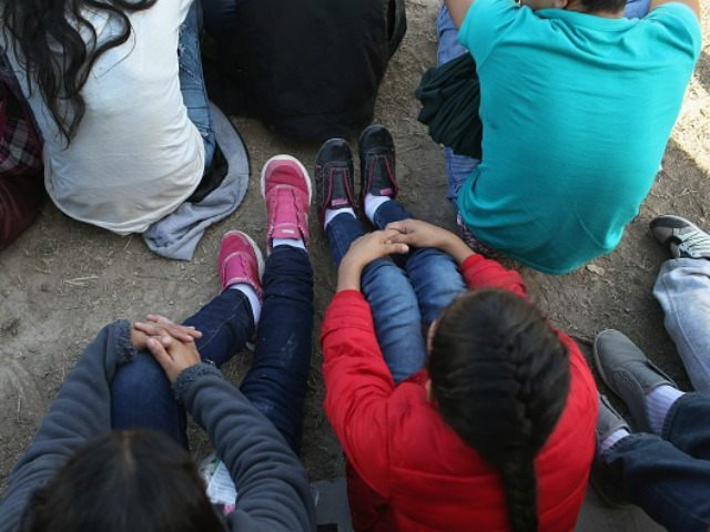 Central American immigrants sit after turning themselves in to U.S. Border Patrol agents on December 8, 2015 near Rio Grande City, Texas. They had just illegally crossed the U.S.-Mexico border into Texas to seek asylum