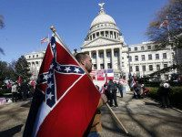 Hjalmberi Shytox of Purvis, Miss., carries a Mississippi state flag in front of the Capitol in Jackson, Miss., Tuesday, Jan. 19, 2016, while participating in a rally in support of keeping the Confederate battle emblem on the state flag. (AP Photo/Rogelio V. Solis)