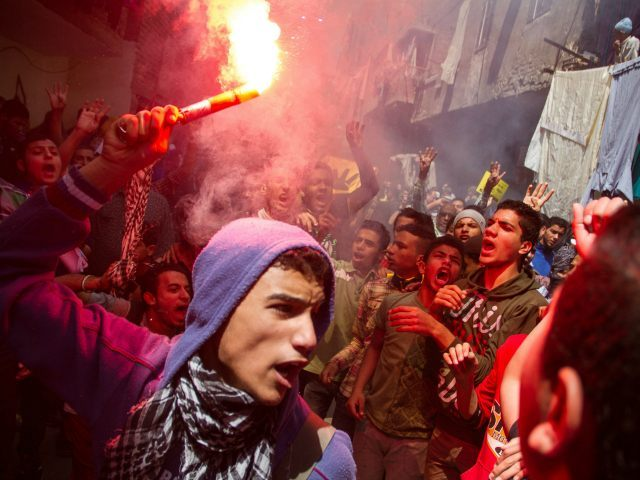 FILE - In this Friday, April 24, 2015 file photo, an Egyptian youth carries a lit flare as supporters of the Muslim Brotherhood gather in the El-Mataria neighborhood of Cairo, Egypt, to protest the 20-year sentence for ousted president Mohammed Morsi and verdicts against other prominent figures of the Brotherhood. (AP Photo/Belal Darder, File)
