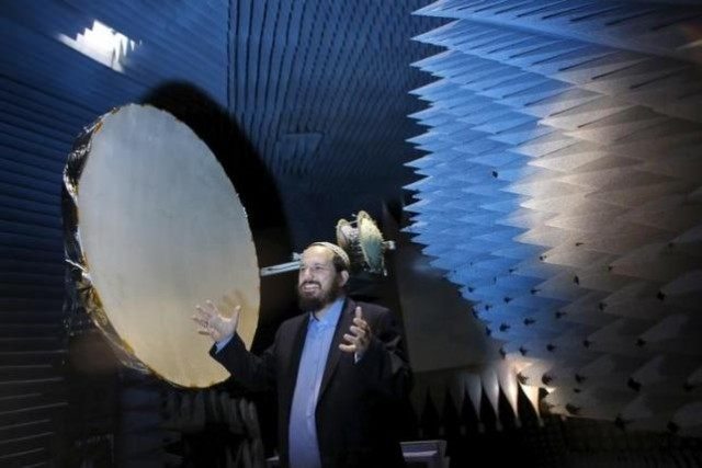 Co-founder of Israeli startup Skyfi, Raz Itzhaki Tamir, gestures during an interview with Reuters in an anechoic chamber where the company performs tests on their development, the first self-correcting antenna that can turn mini-satellites into powerful transmitters covering the globe to provide worldwide internet access, in Rosh Ha'ayin, near Tel …