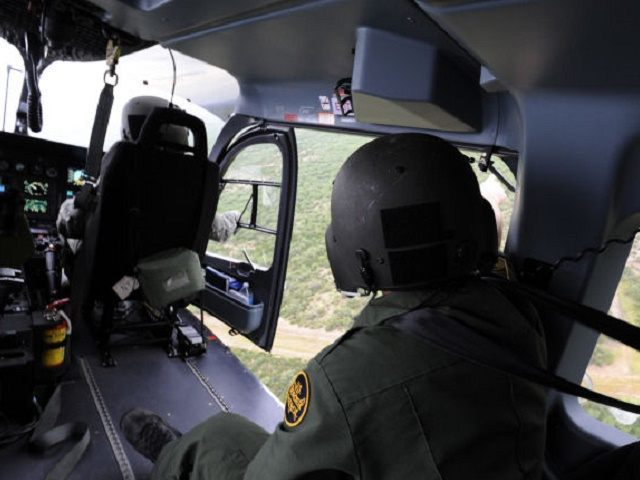 A Border Patrol agent points out an area of possible illegal activity to a National Guard aviator along the Texas-Mexico border July 17, 2013. National Guardsmen from across the country assist Customs and Border Protection in disrupting transnational criminal organizations and drug trafficking organizations by conducting aerial detection and monitoring …