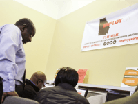 Georgia Department of Labor services specialist Eric Frasier, left, helps a woman with a job search at an unemployment office, Thursday, March 3, 2016, in Atlanta.