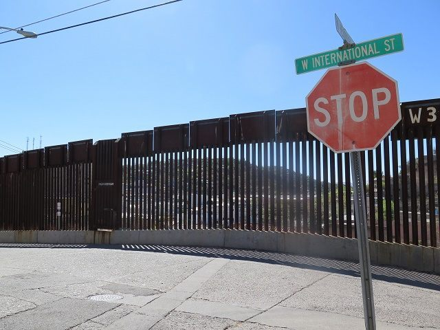 This March 9, 2016 photo shows a stop sign in front of the international border fence in Nogales, Ariz.