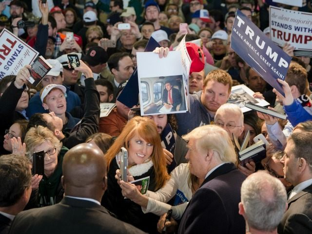 Republican presidential candidate Donald Trump, bottom center right, has his picture taken with attendees during a campaign stop at the Signature Flight Hangar at Port-Columbus International Airport, Tuesday, March 1, 2016, in Columbus, Ohio. (