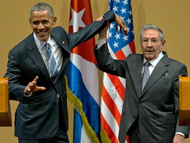 Cuban President Raul Castro, right, lifts up the arm of President Barack Obama at the conclusion of their joint news conference at the Palace of the Revolution, Monday, March 21, 2016, in Havana, Cuba.