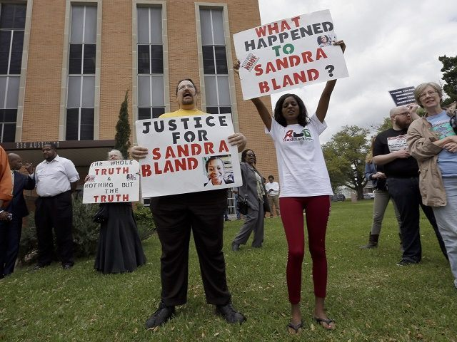 Demonstrators protest outside the courthouse after former Texas state trooper Brian Encinia's arraignment hearing Tuesday, March 22, 2016, in Hempstead, Texas. Encinia, who arrested Sandra Bland, was arraigned on a misdemeanor perjury charge. (AP Photo/David J. Phillip)