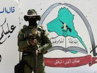 IRAQ, Basra : An Iraqi fighter of the Shiite group Asaib Ahl al-Haq (The League of the Righteous) stands guard outside the militia's headquarters on May 18, 2015 in the Iraqi mainly Shiite southern city of Basra, as Shiite militias converged on Ramadi in a bid to recapture it from …