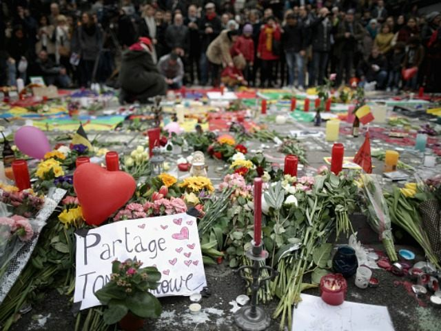 People observe a one minute silence at the Place De La Bourse in honour of the victims of yesterdays' terror attacks on March 23, 2016 in Brussels, Belgium.