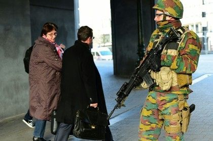 A Belgian soldier stands guard outside Brussels Central Station as people are allowed in small groups of ten to reach the station in order to take their commuter train following attacks in Brussels on March 22, 2016.