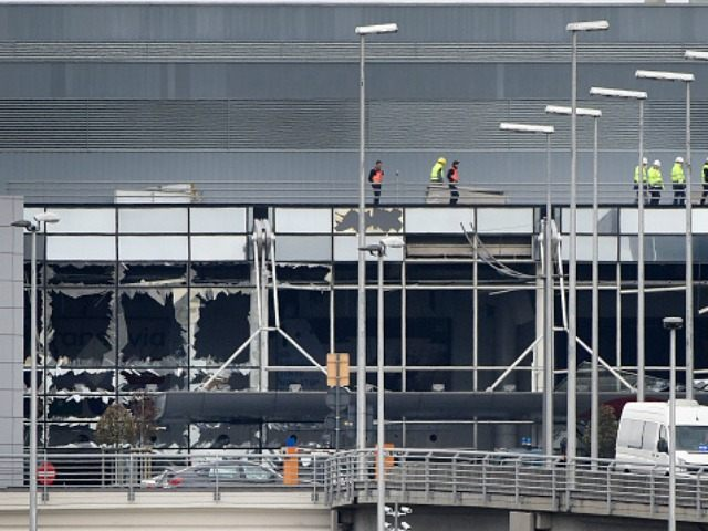 Workers walk on the roof of the damaged facade of Brussels airport in Zaventem on March 23, 2016