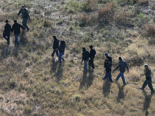 U.S. Border Patrol agents lead undocumented immigrants after capturing them near the U.S.-Mexico border on December 10, 2015 at La Grulla, Texas.