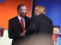 Republican presidential candidates Ben Carson and Donald Trump laugh during a commercial break during the Fox Business Network Republican presidential debate at the North Charleston Coliseum and Performing Arts Center on January 14, 2016 in North Charleston, South Carolina.