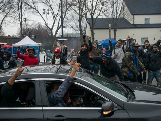 Members of the funeral procession for Jamar Clark join protestors, raising their fists outside the 4th Precinct Minneapolis Police station on November 25, 2015 in Minneapolis, Minnesota.