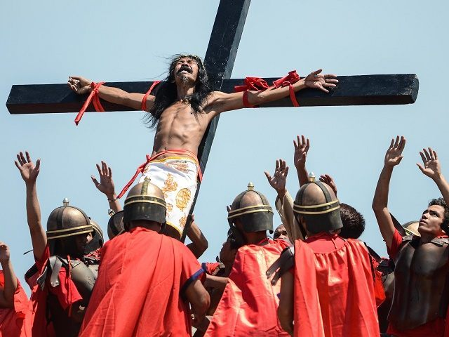 MANILA, PHILIPPINES - APRIL 18: A Catholic devotee nailed to a cross is hoisted by participants during a re-enacment of the crucifixion of Christ on Good Friday on April 18, 2014 in San Pedro Cutud village in Pampanga province, Philippines. At least 18 people were nailed to the cross including …