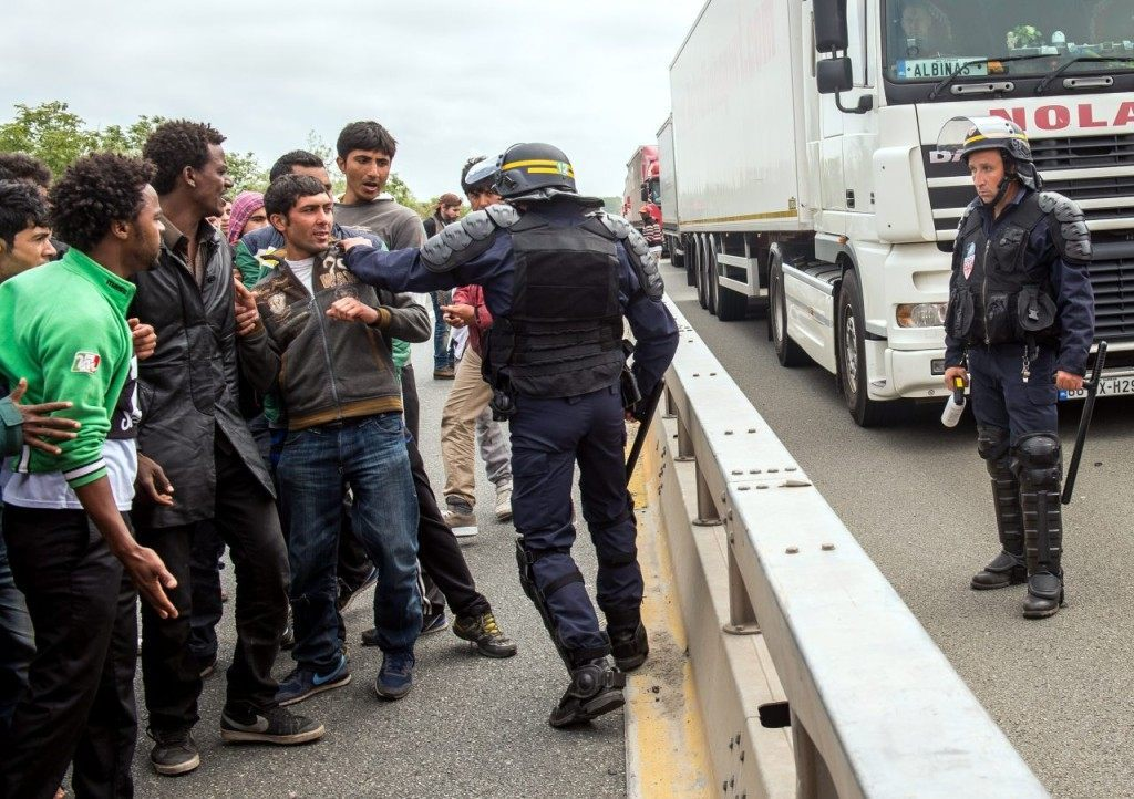 A French riot police officer (CRS) pushes back a man as illegal migrants wait to attempt to hide in lorries heading for England, in the French northern harbour of Calais, on June 17, 2015. AFP PHOTO / PHILIPPE HUGUEN (Photo credit should read PHILIPPE HUGUEN/AFP/Getty Images)