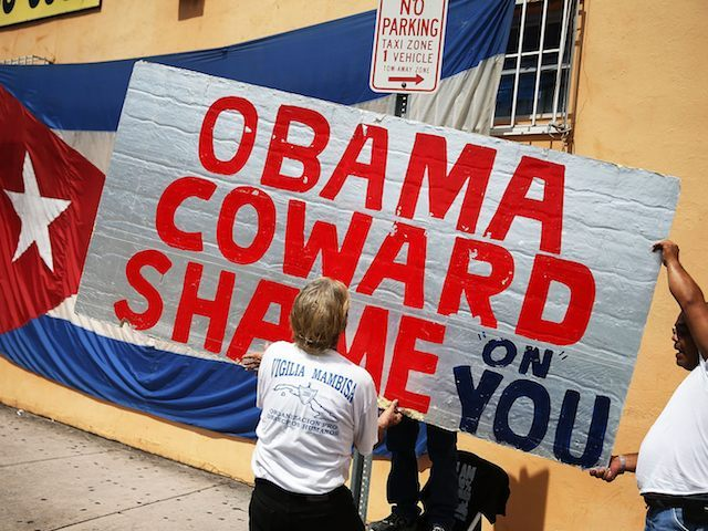 MIAMI, FL - JULY 20: Protestes hang a sign that reads, 'Obama Coward Shame on You', as they show their displeasure, in the Little Havana neighborhood, with the normalization of the Cuban/United States relationship as the Cuban Embassy opens after a 54 year absence in Washington, DC on July 20, …