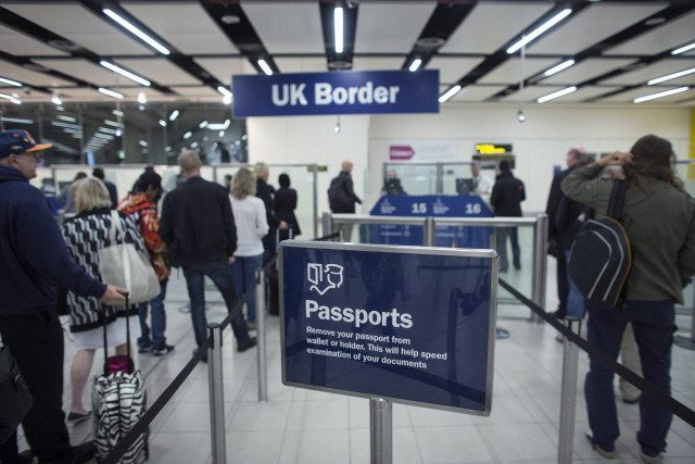 LONDON, ENGLAND - MAY 28: Border Force check the passports of passengers arriving at Gatwick Airport on May 28, 2014 in London, England. Border Force is the law enforcement command within the Home Office responsible for the security of the UK border by enforcing immigration and customs controls on people …