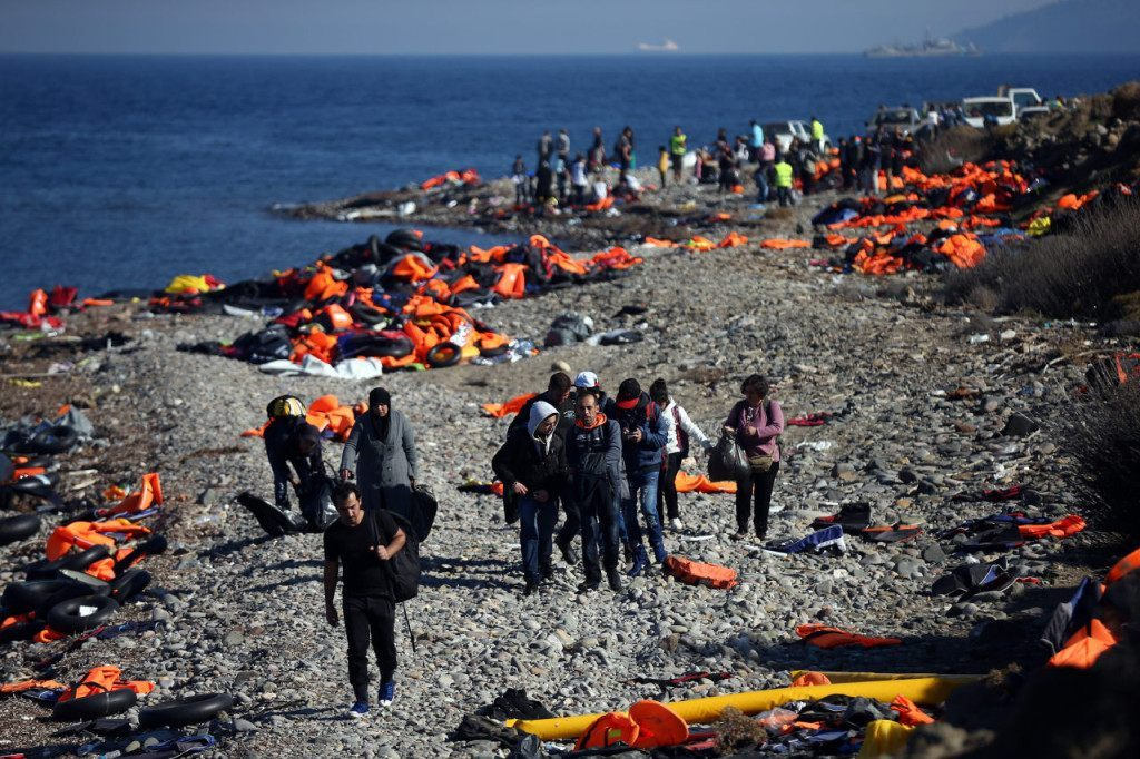 SIKAMINIAS, GREECE - NOVEMBER 14: Migrants walk along a beach after making the crossing from Turkey to the Greek island of Lesbos on November 14, 2015 in Sikaminias, Greece. Rafts and boats continue to make the journey from Turkey to Lesbos each day as thousands flee conflict in Iraq, Syria, Afghanistan and other countries. Over 500,000 migrants have entered Europe so far this year and approximately four-fifths of those have paid to be smuggled by sea to Greece from Turkey, the main transit route into the EU. Most of those entering Greece on a boat from Turkey are from the war zones of Syria, Iraq and Afghanistan. (Photo by Carl Court/Getty Images)