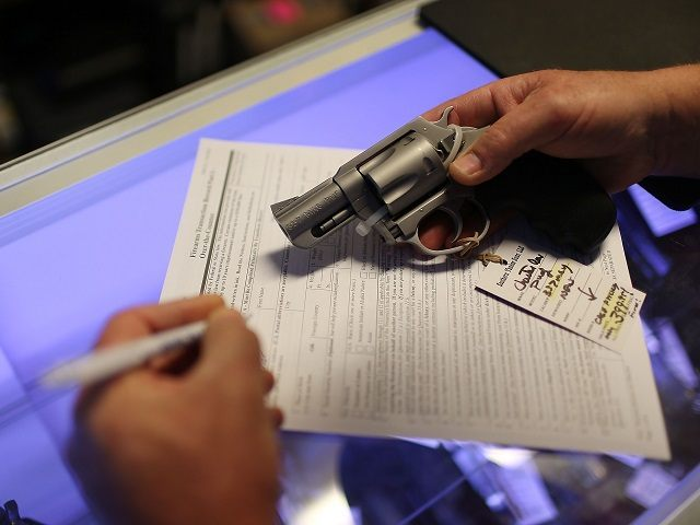 Mark O'Connor fills out his Federal background check paperwork as he purchases a handgun at the K&W Gunworks store on the day that U.S. President Barack Obama in Washington, DC announced his executive action on guns on January 5, 2016 in Delray Beach, Florida. President Obama announced several measures that …