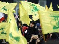 Supporters wave the flag of Lebanon's Shiite movement Hezbollah as they watch the movement's leader Hassan Nasrallah give a televised speech from an undisclosed location during a rally held in the southern suburbs of Beirut on February 16, 2016, to mark the anniversary of the Israeli killings of Lebanese Hezbollah …