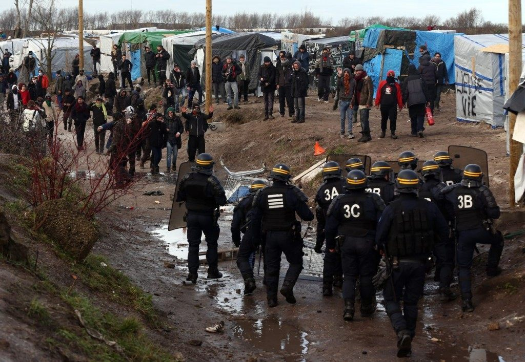 CALAIS, FRANCE - FEBRUARY 29: Police officers confront migrants and activists as part of the 'jungle' migrant camp is cleared on February 29, 2016 in Calais, France The French authorities have begun dismantling part of the migrant encampment in the northern French town of Calais and relocating people to purpose-built accommodation nearby. (Photo by Carl Court/Getty Images)