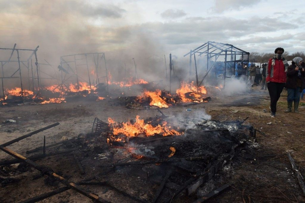 "Shacks are burning during the dismantling of half of the ""Jungle"" migrant camp in the French northern port city of Calais, on February 29, 2016. Clashes broke out between French riot police and migrants on February 29 as bulldozers moved into the grim shantytown on the edge of Calais known as the ""Jungle"" to start destroying hundreds of makeshift shelters. AFP PHOTO / PHILIPPE HUGUEN / AFP / PHILIPPE HUGUEN (Photo credit should read PHILIPPE HUGUEN/AFP/Getty Images)"