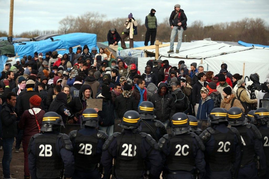 CALAIS, FRANCE - FEBRUARY 29: Police officers face activists and migrants as part of the 'jungle' migrant camp is cleared on February 29, 2016 in Calais, France The French authorities have begun dismantling part of the migrant encampment in the northern French town of Calais and relocating people to purpose-built accommodation nearby. (Photo by Carl Court/Getty Images)
