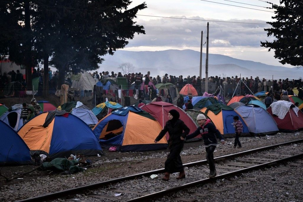 TOPSHOT - A woman and a boy walk along the railway track as refugees and migrants (Rear) wait for food in a makeshift camp at the Greek Macedonian borders near the Greek village of Idomeni, on March 4 , 2016. The humanitarian crisis was most acute at the Idomeni crossing where around 12,000 people were stranded after Austria and the Balkan states imposed a cap on entries, triggering a rapid build-up in Greece. / AFP / LOUISA GOULIAMAKI (Photo credit should read LOUISA GOULIAMAKI/AFP/Getty Images)