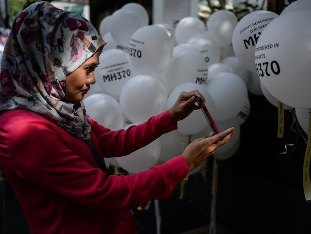 A woman takes pictures of balloons with names of the missing Malaysia Airlines ill-fated flight MH370 during a memorial event in Kuala Lumpur on March 6, 2016. Families of those lost on MH370 are preparing mark the upcoming second anniversary of when the Malaysia Airlines flight disappeared on March 8, 2014. / AFP / MOHD RASFAN (Photo credit should read MOHD RASFAN/AFP/Getty Images)