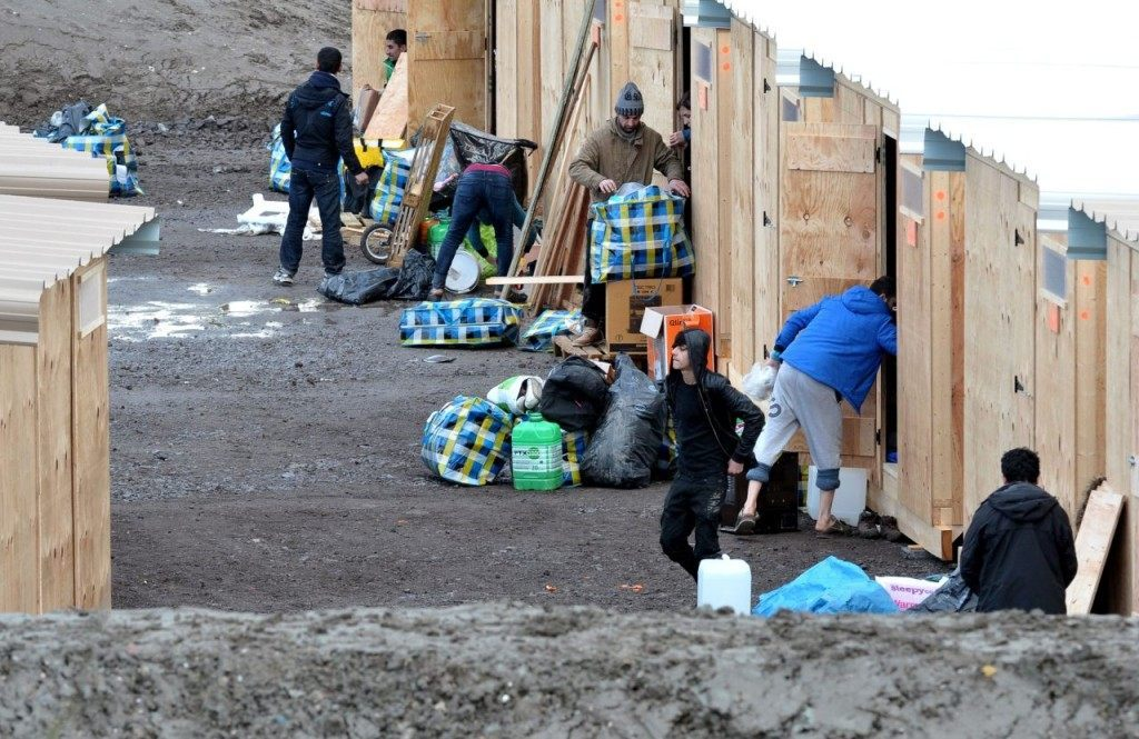 "Migrants and refugees arrive in the first international-standard refugee camp on March 7, 2016 in Grande-Synthe, northern France. France opened its first international-standard refugee camp in the teeth of official opposition on March 7 while demolition continued at the nearby Calais ""Jungle"" camp. The new camp, featuring some 200 heated wooden cabins and proper toilets and showers, has been built by Doctors Without Borders (MSF) with the support of the local town hall, despite opposition from the French government. / AFP / FRANCOIS LO PRESTI (Photo credit should read FRANCOIS LO PRESTI/AFP/Getty Images)"