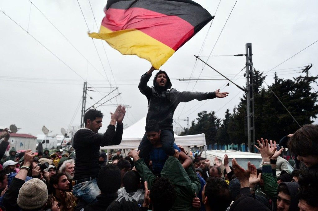 TOPSHOT - A man sits on the shoulders of another man and waves a German flag as people protest under the rain to call for the opening of the borders near the village of Idomeni where thousands of refugees and migrants are stranded on March 7, 2016. EU leaders held a summit with Turkey's prime minister on March 7 in order to back closing the Balkans migrant route and urge Ankara to accept deportations of large numbers of economic migrants from overstretched Greece. / AFP / LOUISA GOULIAMAKI (Photo credit should read LOUISA GOULIAMAKI/AFP/Getty Images)
