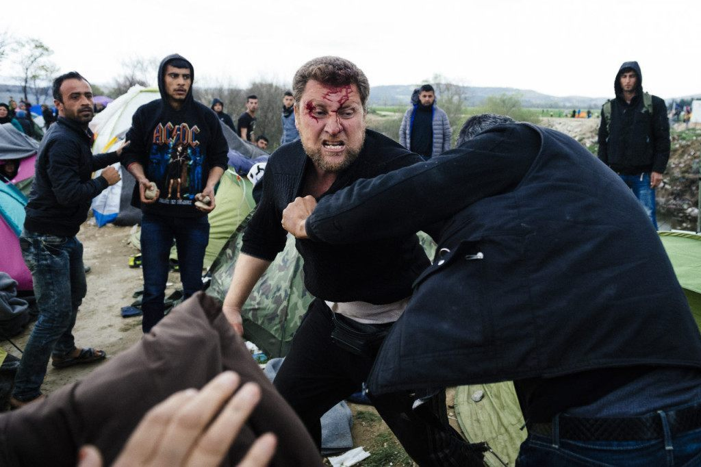Migrants fight at a makeshift camp at the Greek-Macedonian border near the Greek village of Idomeni on March 7, 2016, where thousands of refugees and migrants are stranded. European Unions leaders held a summit with Turkey's prime minister on March 7 in order to back closing the Balkans migrant route and urge Ankara to accept deportations of large numbers of economic migrants from overstretched Greece. More than one million refugees and migrants have arrived in Europe since the start of 2015 -- the majority fleeing the war in Syria -- with nearly 4,000 dying while crossing the Mediterranean. / AFP / DIMITAR DILKOFF (Photo credit should read DIMITAR DILKOFF/AFP/Getty Images)