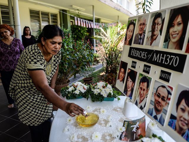 "A school teacher lights a candle as she pray for passengers of missing Malaysia Airlines flight MH370 in Petaling Jaya on March 8, 2016. Malaysia and Australia said they remained ""hopeful"" of solving the mystery of flight MH370 as the second anniversary of the plane's disappearance arrived on March 8 with no end in sight for devastated families. / AFP / MOHD RASFAN (Photo credit should read MOHD RASFAN/AFP/Getty Images)"