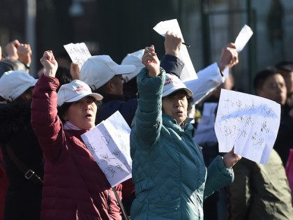 Relatives of passengers missing on Malaysia Airlines MH370 chant outside the Malaysian embassy in Beijing on March 8, 2016. Relatives of missing passengers gathered at the embassy to demand more information on the second anniversary of the flight from Kuala Lumpur to Beijing which went missing on March 8, 2014. …