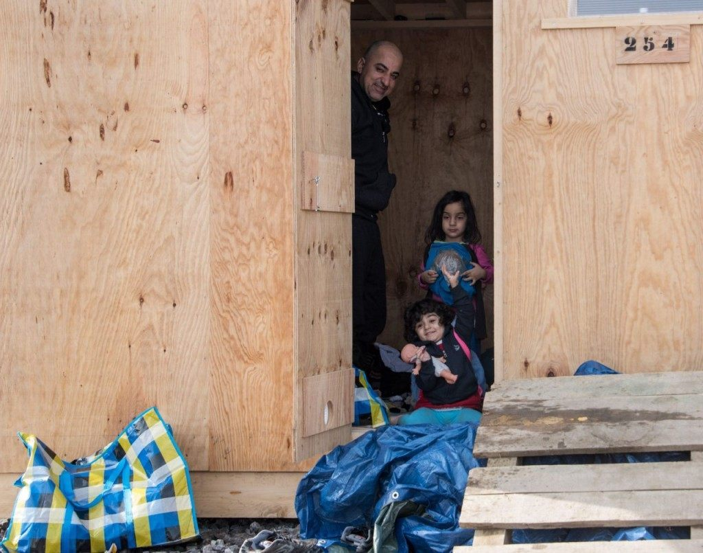 Iraqi Kurds look out from a wooden cabin on March 8, 2016, in Grande-Synthe, northern France, as they settle in France's first international-standard refugee camp, after coming from a nearby site where migrants and refugees have been living in miserable conditions. France's first international-standard refugee camp opened March 8 despite opposition from Paris but the central government's local representative raised safety concerns that could suspend its operations. The new camp, featuring some 200 heated wooden cabins and proper toilets and showers, has been built by Doctors Without Borders (MSF) with the support of the local town hall, despite opposition from the French government. / AFP / DENIS CHARLET (Photo credit should read DENIS CHARLET/AFP/Getty Images)