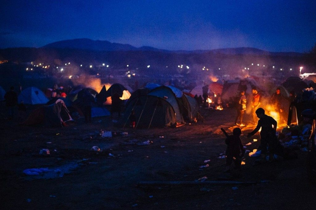 "A family sits around a bonfire among other migrants and refugees, at the makeshift camp of the Greek-Macedonian border, near the village of Idomeni, on March 8, 2016, where thousands of refugees and migrants are trapped by the Balkans border blockade. The head of the UN refugee agency on March 8 said he was ""deeply concerned"" by a proposed deal between the EU and Ankara to curb the migrant crisis that would involve people being sent back to Turkey. / AFP / DIMITAR DILKOFF (Photo credit should read DIMITAR DILKOFF/AFP/Getty Images)"