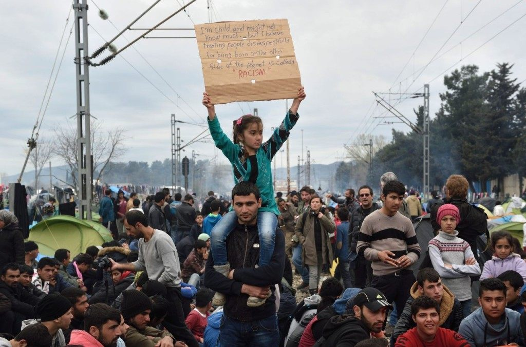 Migrants and refugees take part in a protest asking for the opening of the border on March 12, 2016, in a makeshift camp at the Greek-Macedonian border, near the Greek village of Idomeni, where thousands of refugees and migrants are stranded by the Balkan border blockade. Greece aims to deal swiftly with the migrant overflow at the Idomeni refugee camp on the Greek-Macedonian border where some 12,000 people are camping in miserable conditions waiting to cross. / AFP / DANIEL MIHAILESCU (Photo credit should read DANIEL MIHAILESCU/AFP/Getty Images)