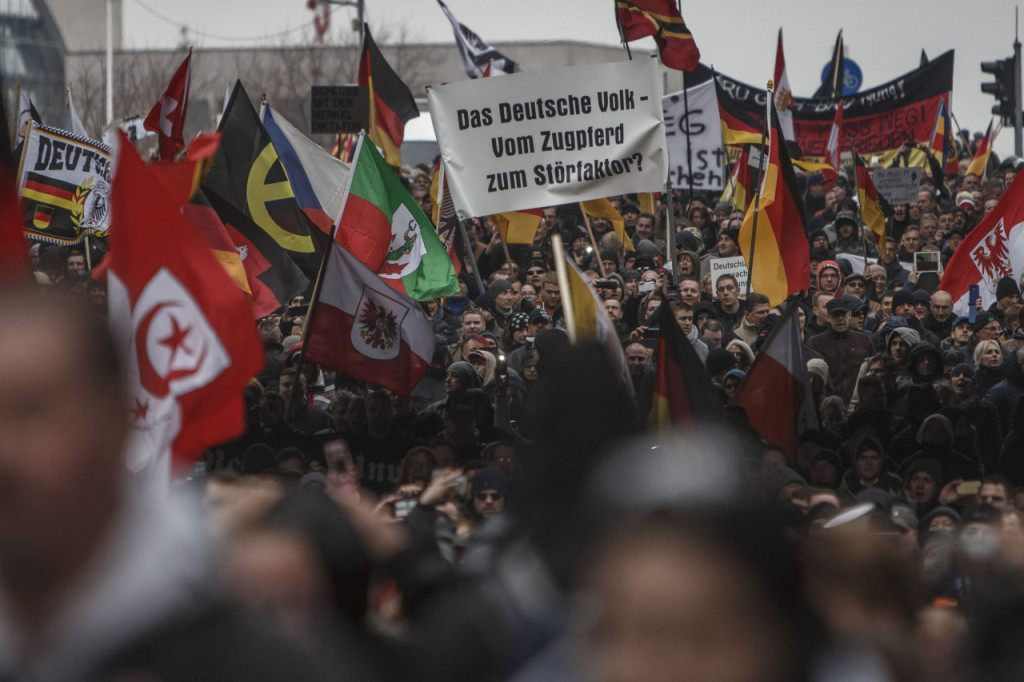 BERLIN, GERMANY - MARCH 12: Right-wing activists gather to march in the city center and protest against German Chancellor Angela Merkel on March 12, 2016 in Berlin, Germany. Germany will hold state elections in three states tomorrow and the right-leaning populist Alternative fuer Deutschland (Alternative for Germany, AfD) political party will very likely gain seats in all three state parliaments. AfD leaders however distanced themselves from today's right-wing march and urged AfD supporters not to participate. Right-wing groups are seeking to profit from the unease of many Germans with Merkel's liberal immigration policy that resulted in 1.1 million migrants and refugees arriving in Germany in 2015. (Photo by Carsten Koall/Getty Images)