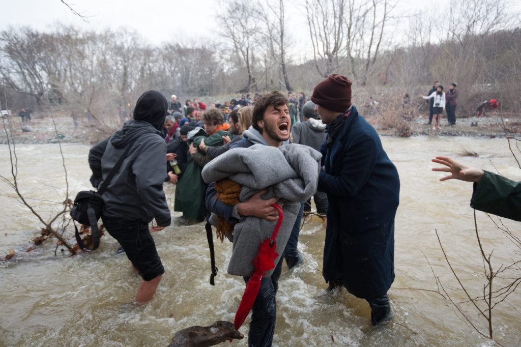 IDOMENI, GREECE - MARCH 14: Migrants cross a river as they try to walk to the Macedonian border after deciding to leave the Idomeni refugee camp on March 14, 2016 in Idomeni, Greece. The decision by Macedonia to close its border to migrants on Wednesday has left thousands of people stranded at the Greek transit camp. The closure, following the lead taken by neighbouring countries, has effectively sealed the so-called western Balkan route, the main migration route that has been used by hundreds of thousands of migrants to reach countries in Western Europe such as Germany. Humanitarian workers have described the conditions at the camp as desperate, which has been made much worse by recent bouts of heavy rain. (Photo by Matt Cardy/Getty Images)