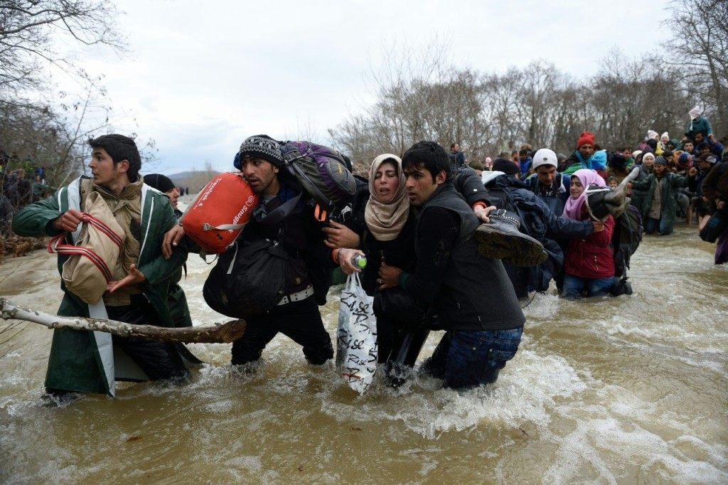 Refugees and migrants try cross a river on their way to Macedonia from a makeshift camp at the Greek-Macedonian border, near the Greek village of Idomeni on March 14, 2016, where thousands of refugees and migrants are stranded by the Balkan border blockade. More than 14,000 people are stuck on the Greek side of the border in an overcrowded camp at Idomeni after the main migrant route to western Europe through the Balkans was effectively shut down last week. / AFP / DANIEL MIHAILESCU (Photo credit should read DANIEL MIHAILESCU/AFP/Getty Images)