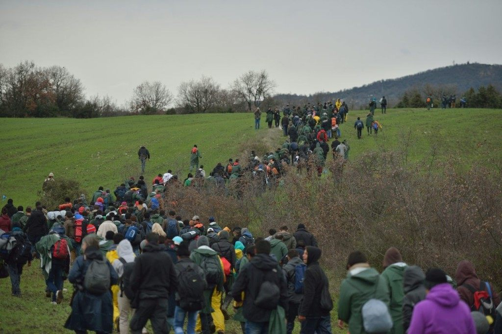 Refugees walk across fields as they make their way to Macedonia from a makeshift camp at the Greek-Macedonian border, near the Greek village of Idomeni on March 14, 2016, where thousands of refugees and migrants are stranded by the Balkan border blockade. Over 1000 refugees left the Idomeni camp on March 14, at noon to find a way to Macedonia. The German and Greek leaders blasted Balkan countries for shutting their borders to migrants ahead of an EU ministers meeting on March 10. Greek authorities said there were 41,973 asylum seekers in the country, including some 12,000 stuck at Idomeni on the closed Macedonian border. / AFP / DANIEL MIHAILESCU (Photo credit should read DANIEL MIHAILESCU/AFP/Getty Images)