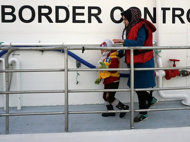 A woman and her child disembarks from a Norwegian Frontex vessel at the port of Mytilene in the island of Lesbos , on March 16, 2016. The Nowergian vessel saved some 250 refugees and migrants who attempted the perilious crossing from Turkey to the Greek island on Lesbos European leaders …
