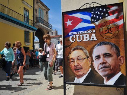 Tourists walk next to a poster of Cuban President Raul Castro and US president Barack Obama in Havana, on March 18, 2016. US president Barack Obama touches down in Havana on Sunday to cap a long-unimaginable rapprochement with Cuba and burnish a presidential legacy dulled by Middle East quagmires and …